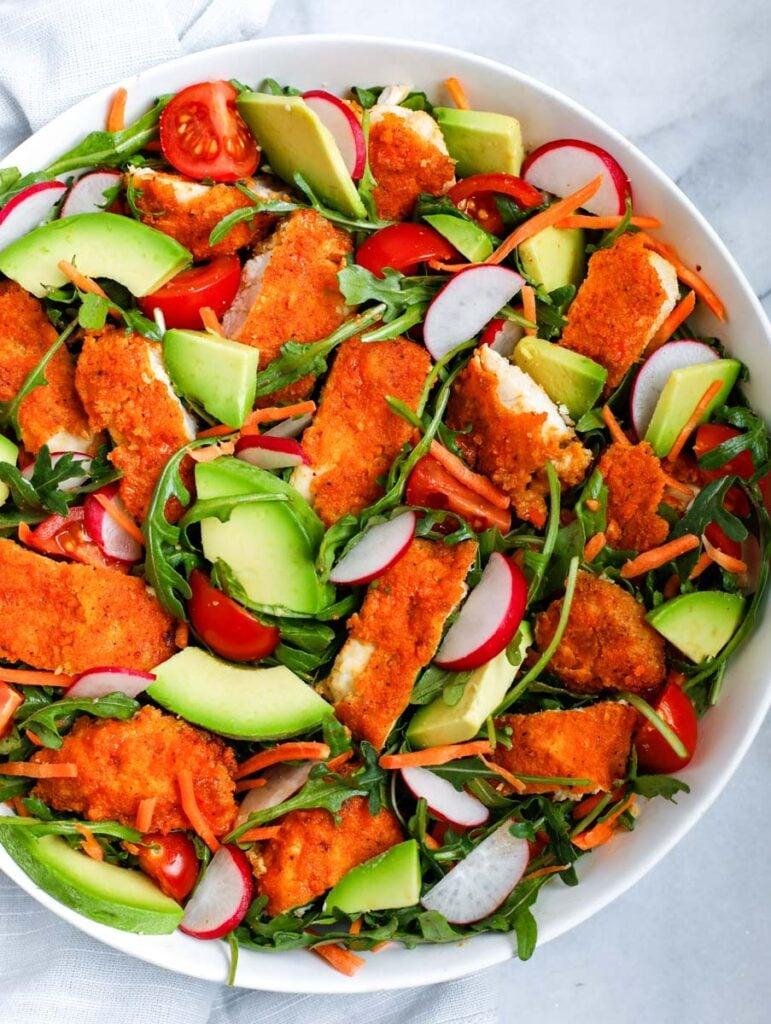 Arugula chicken and veggies in a white bowl.