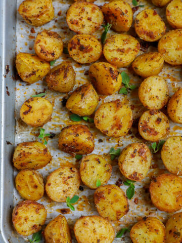 Top down shot of oven roasted baby potatoes on a sheet pan.