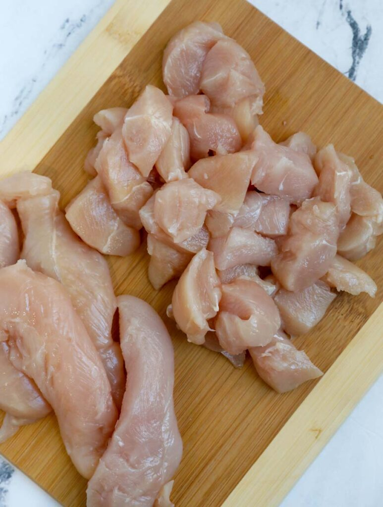 raw chicken cubes on a cutting board