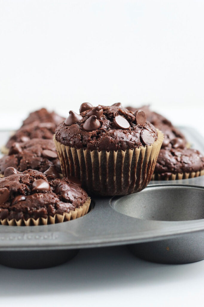 Close up of double chocolate chip muffins on top of a muffin mold.