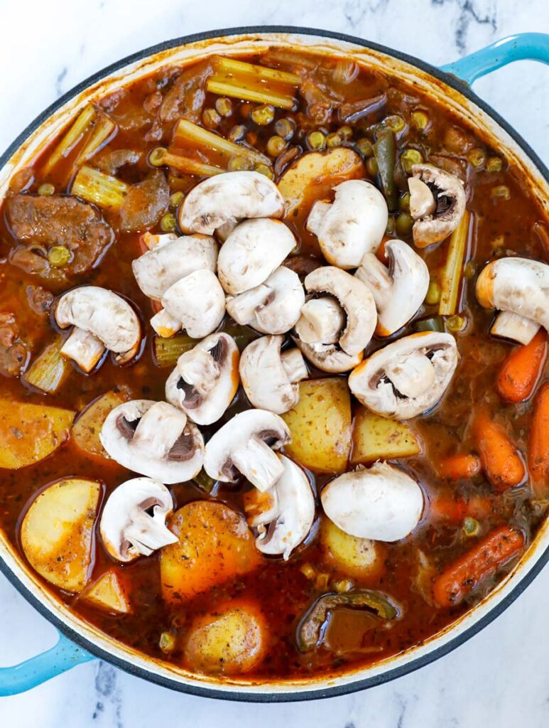 Vegetables and beef in a pot.