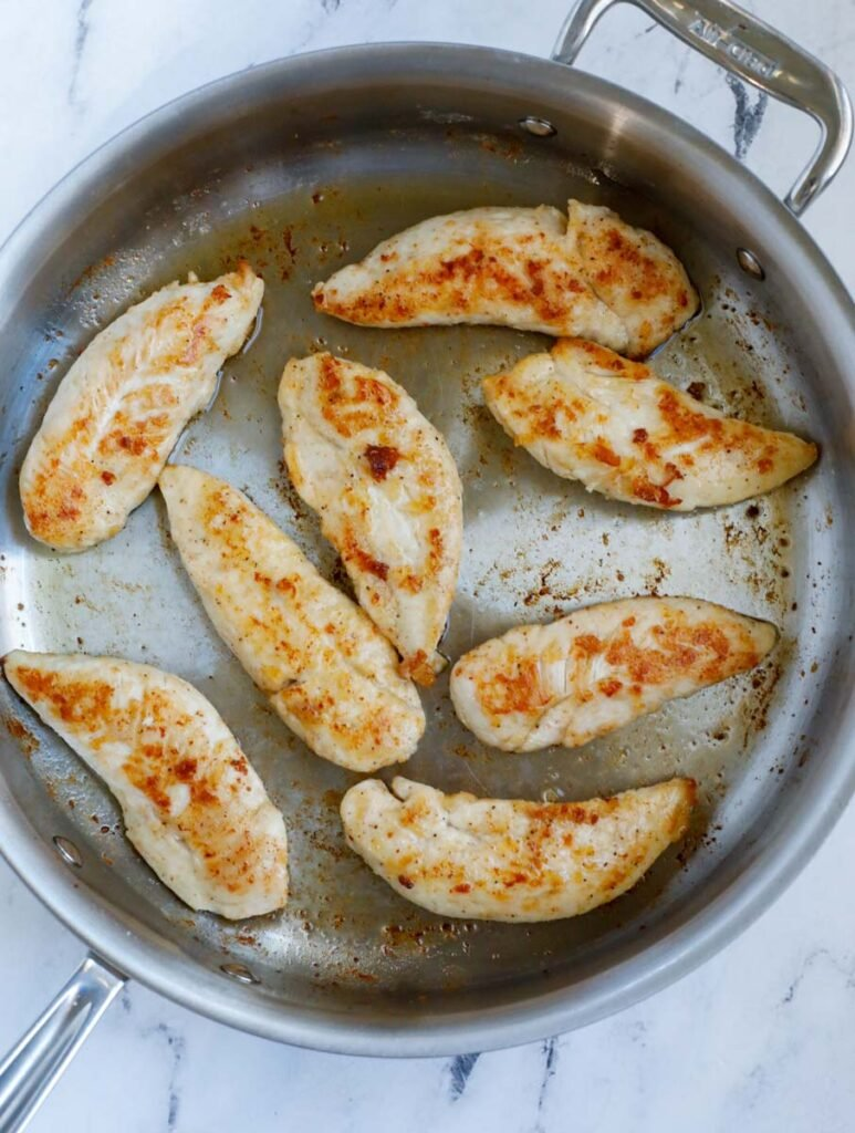 Chicken turning golden in a pan.