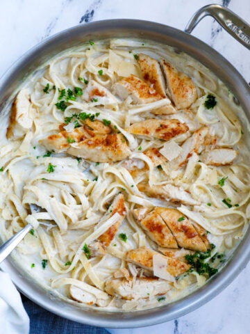 Top down shot of creamy chicken alfredo stirred in a pot.