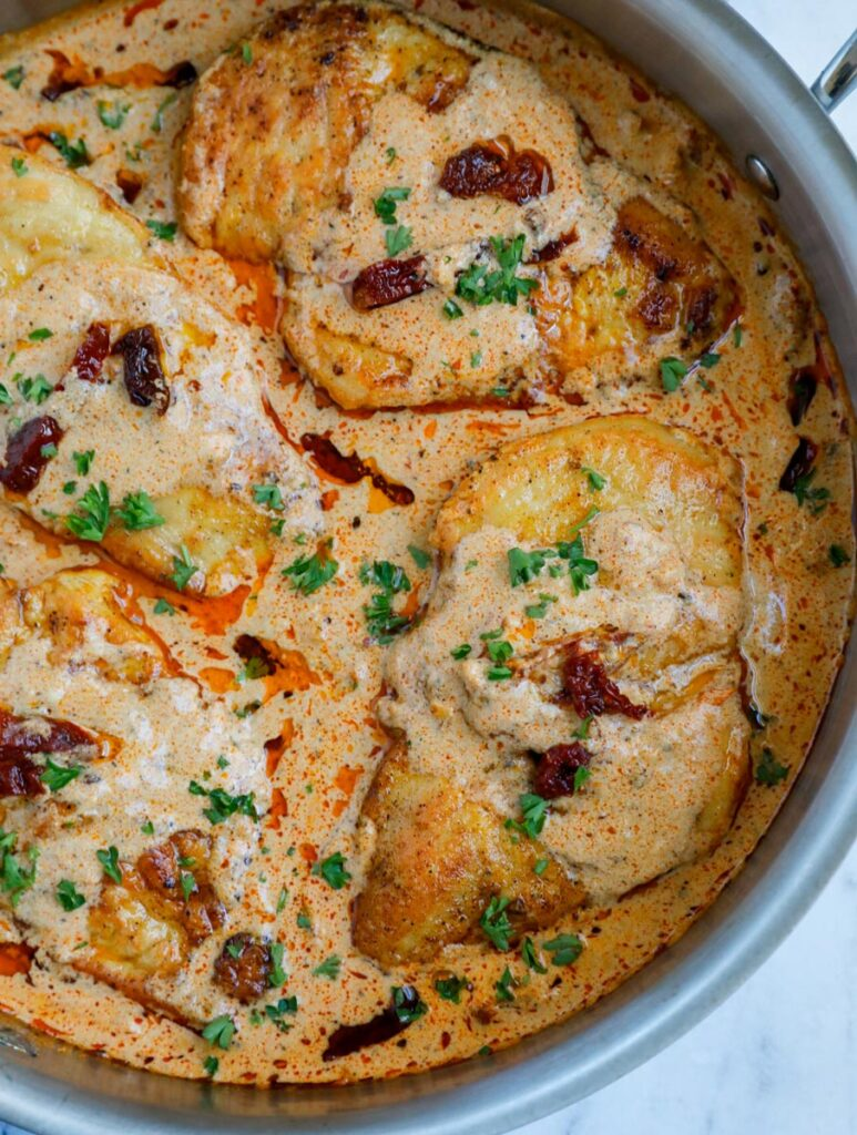 Close up of multiple chicken breast in cajun sauce.