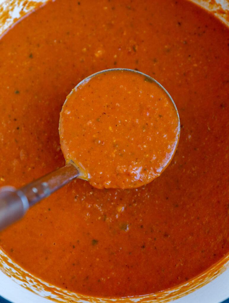 A ladle of creamy tomato soup.