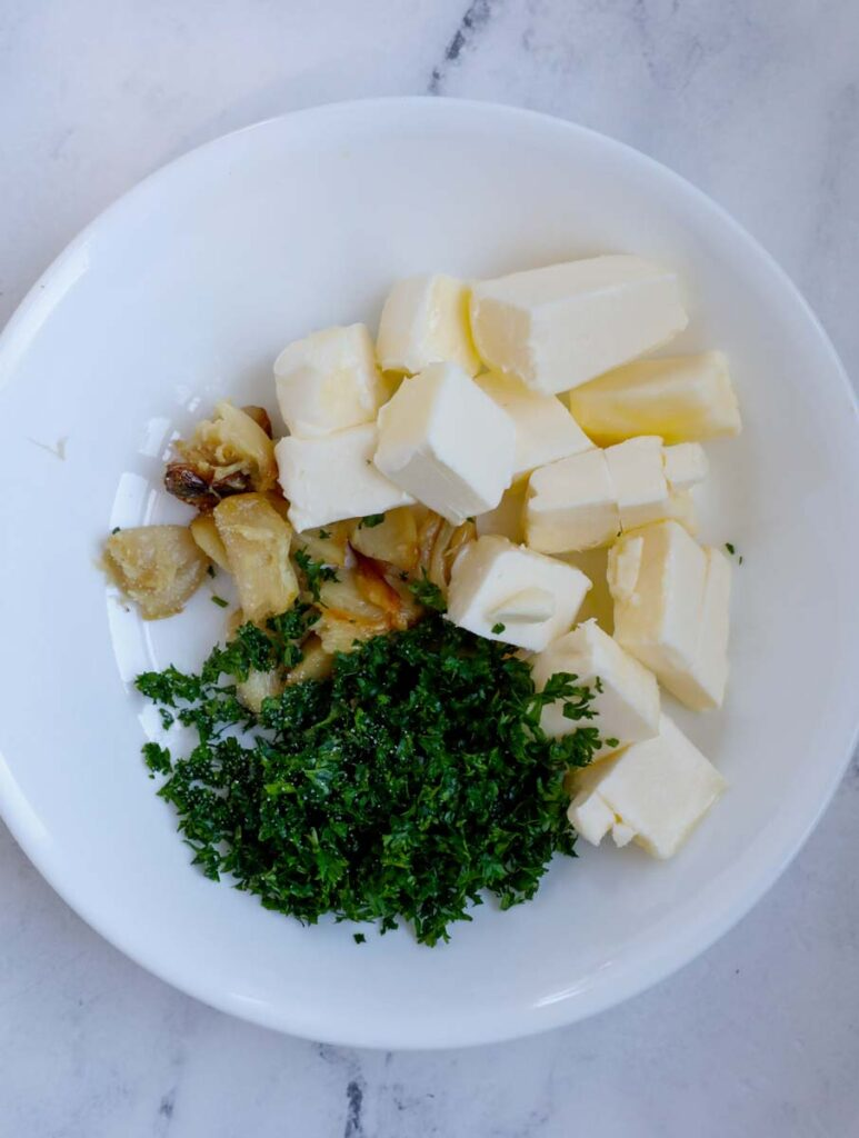 Herbs, butter and garlic in a bowl.
