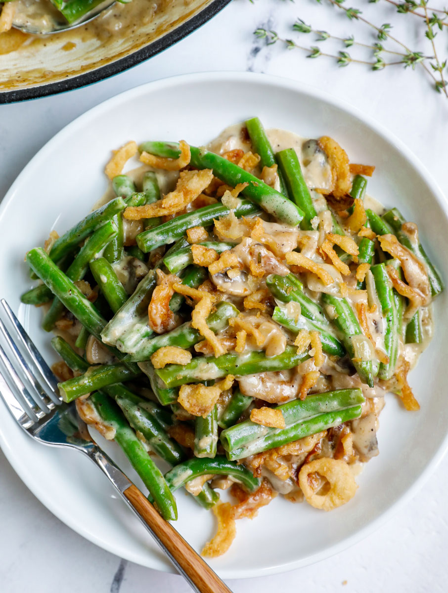 Top down shot of green bean casserole on a white plate.
