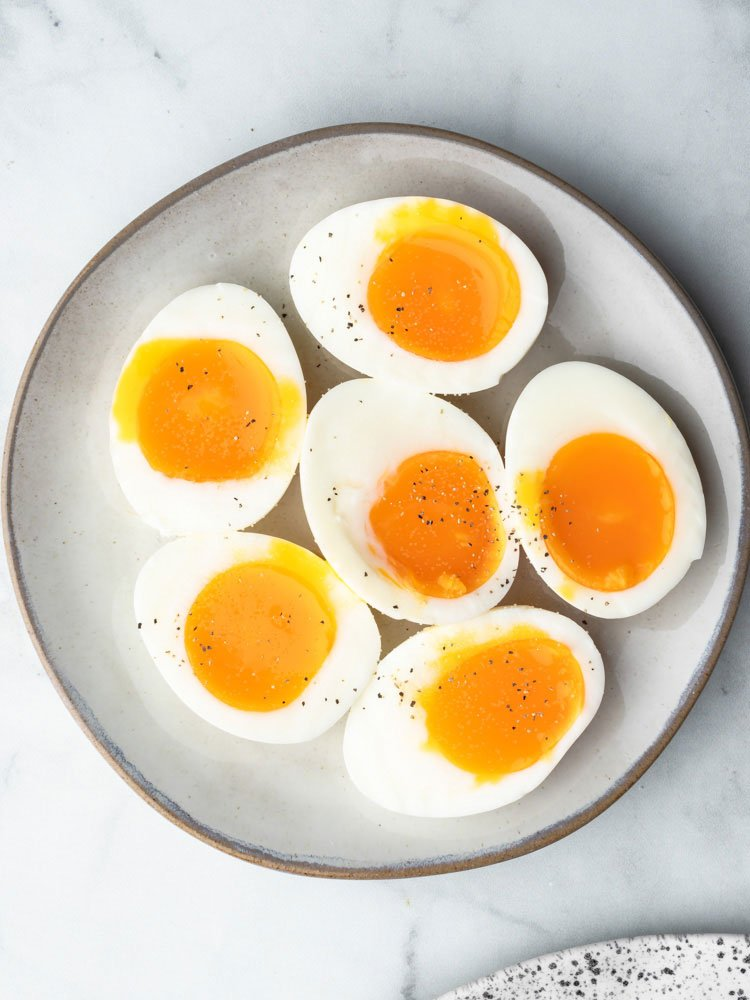 soft boiled eggs cut in half to show the runny yolk center on a plate
