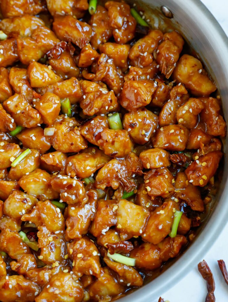 Close up of a skillet with bite sized pieces of general tso chicken.