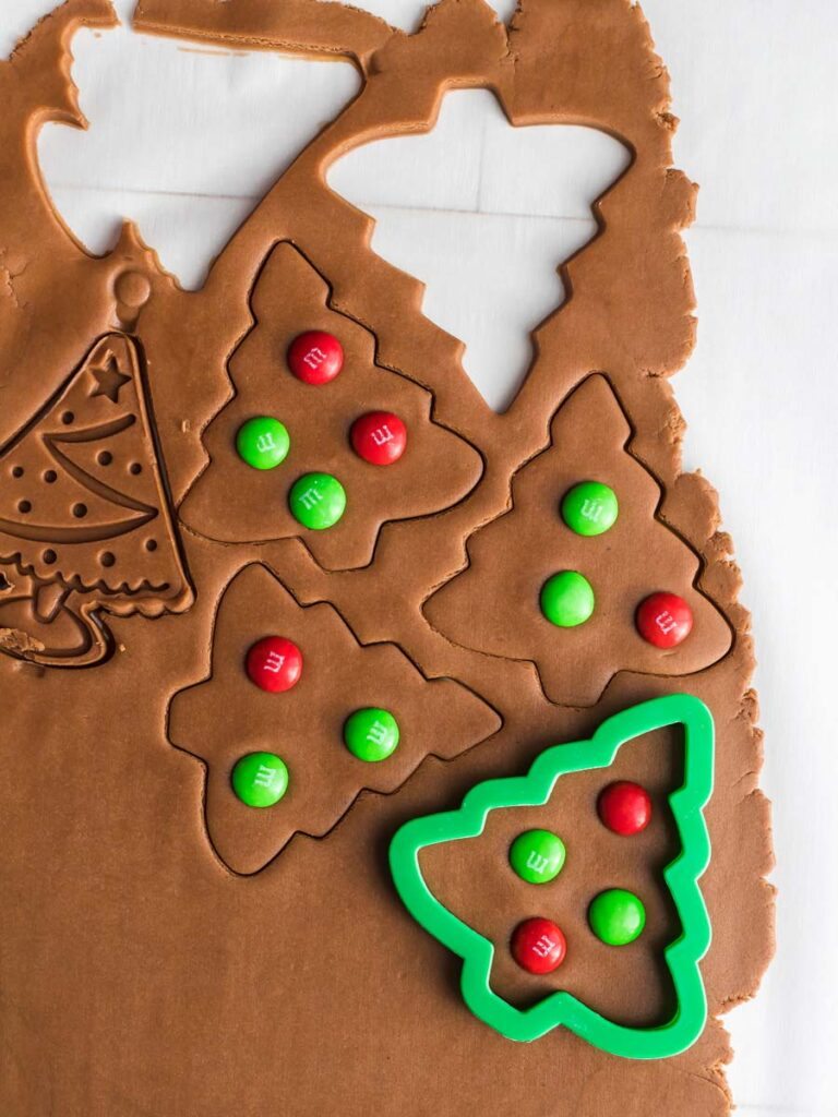 Cutting out tree shapes from dough.