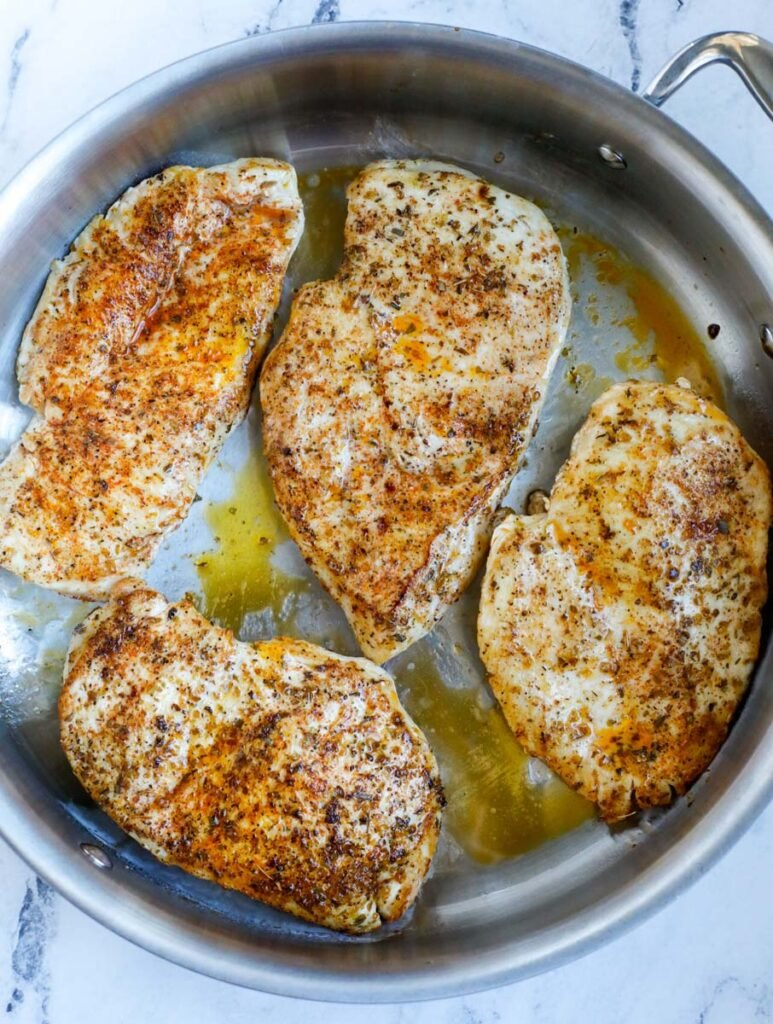 Top down shot of chicken breasts in a pot.