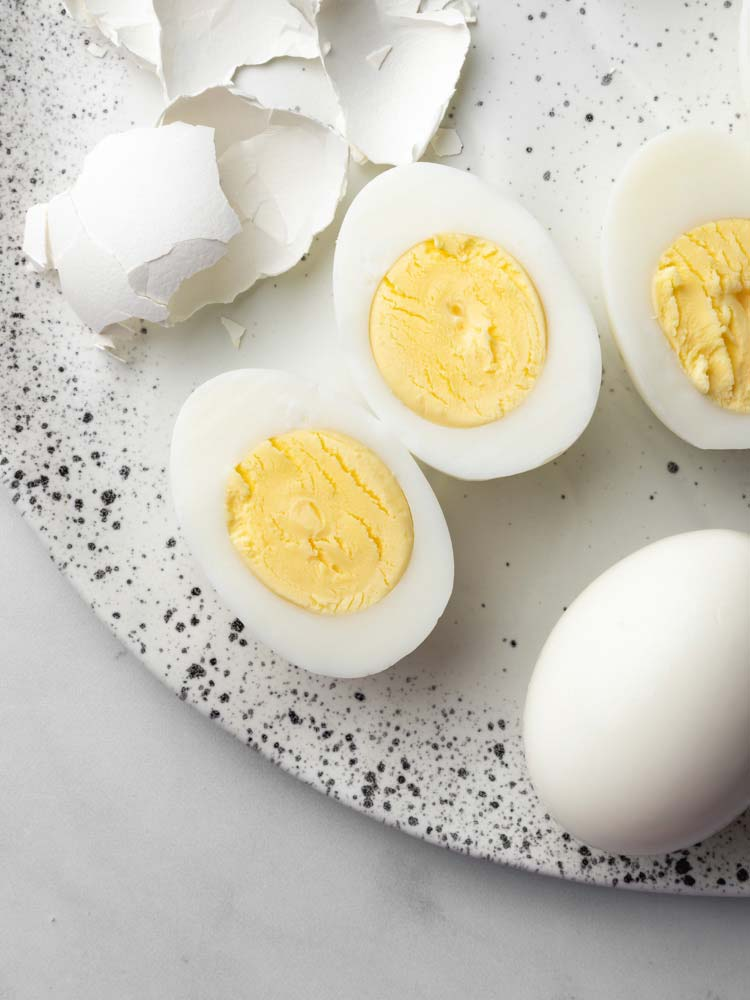 a hard boiled egg sliced in the middle showing the yolk.