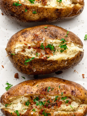 top down close up shot of baked potatoes topped with bacon and parsley