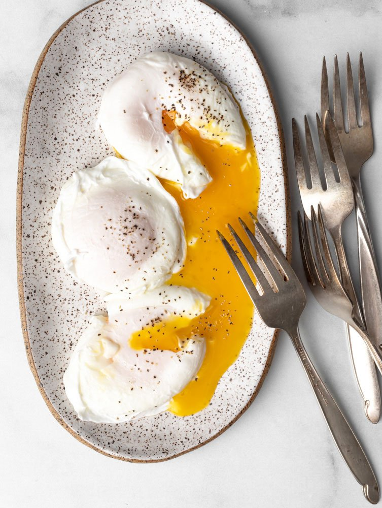 three poached egg on a plate with egg yolks oozing out