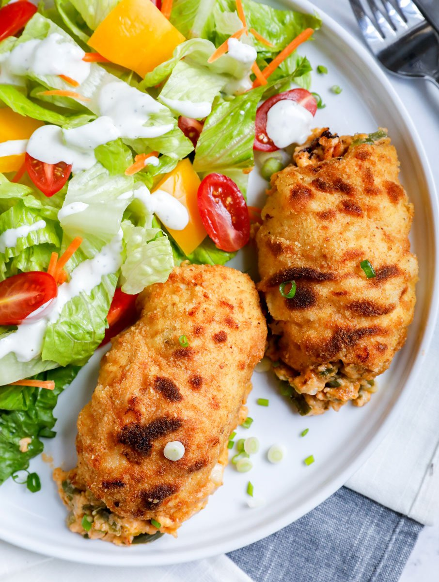 Top down shot of stuffed chicken with salad.
