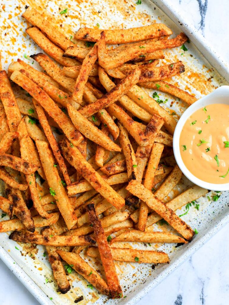 Baked jicama fries on a baking tray with dip