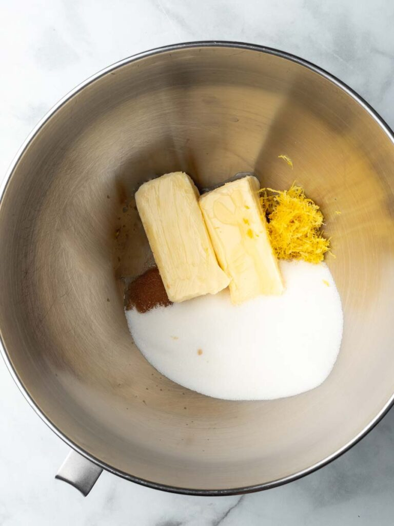 A mixing bowl with sugar, butter, lemon zest, and vanilla extract.