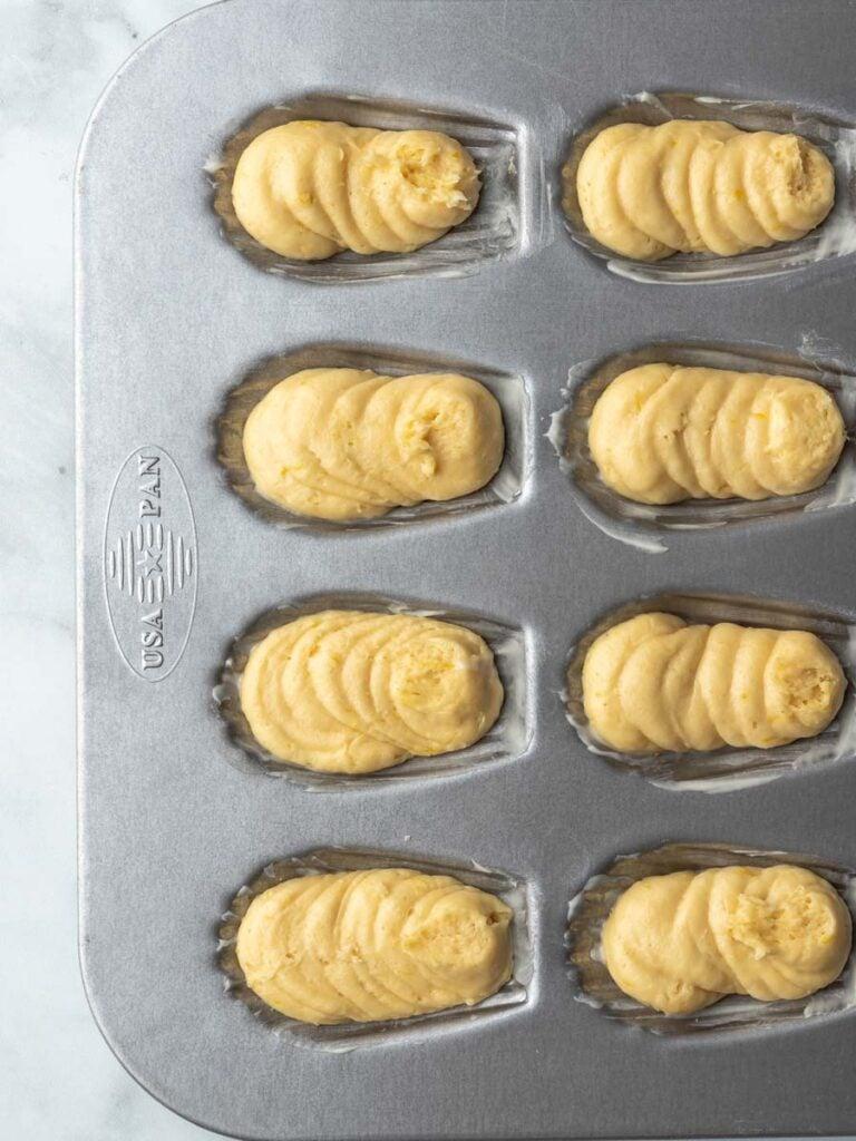 Lemon madeleines batter inside of a pan.