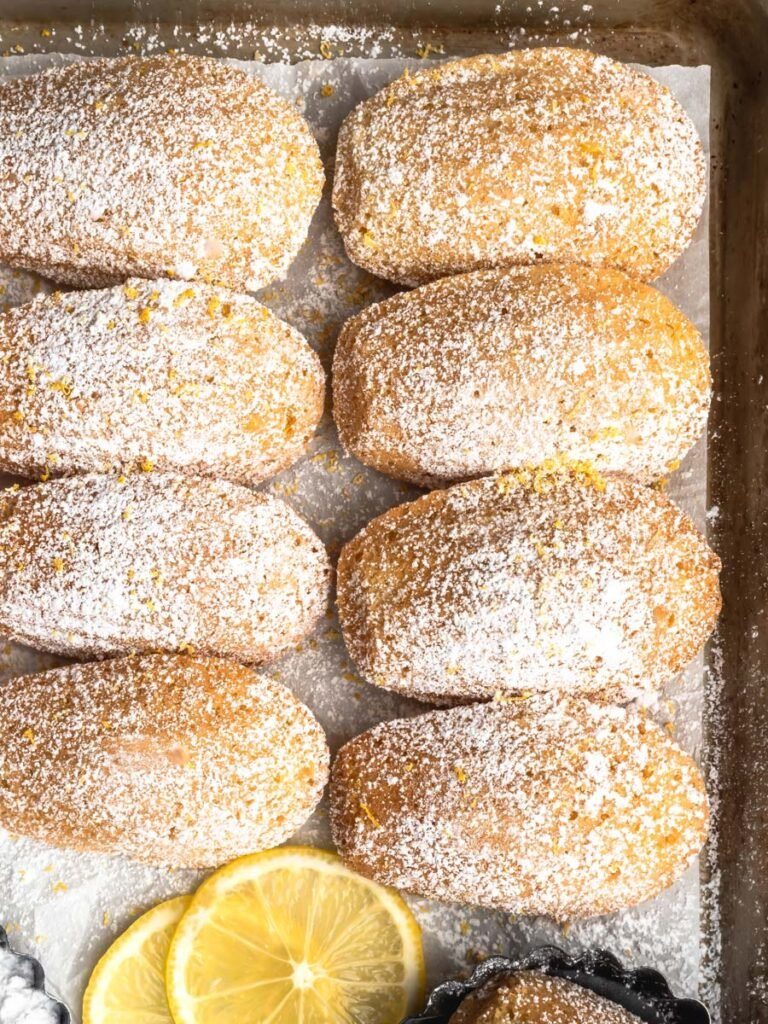Close up of lemon madeleines on a sheet pan with powdered sugar dusted over top.