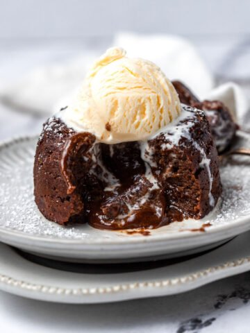 A lava cake cut opened with a scoop of ice cream on top.