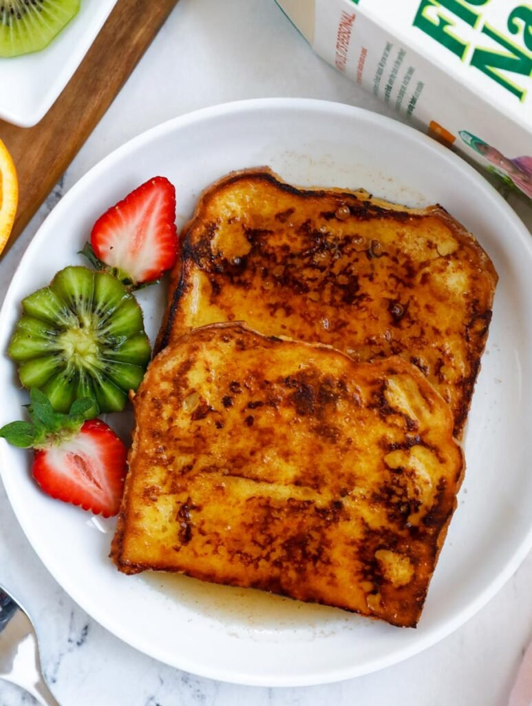 Orange french toast on a plate served with a kiwi and sliced strawberry.