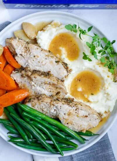 plate of oven baked turkey with mashed potatoes, gravy, and vegetables