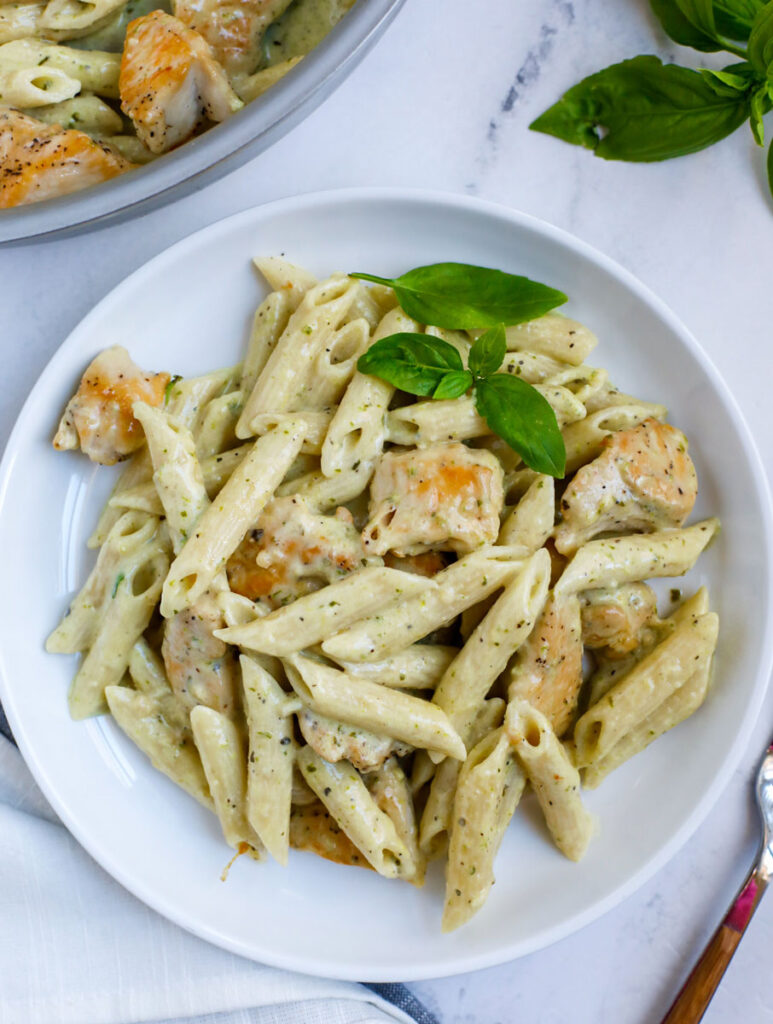 A plate of pesto chicken pasta topped with fresh basil.