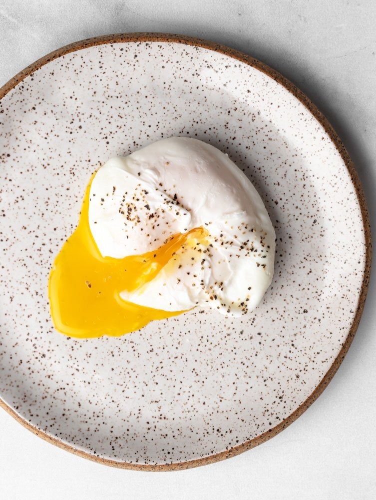 poached egg on a plate, yolk cut through and seasoned with black pepper