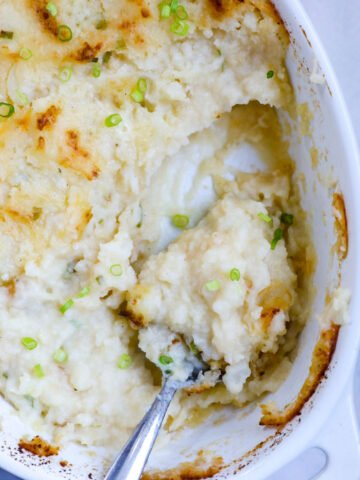 Top down view of mashed potatoes in a baking dish with a portion taken out.