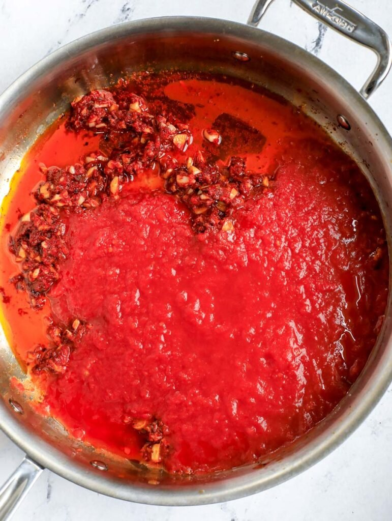 Adding tomato sauce to pot.
