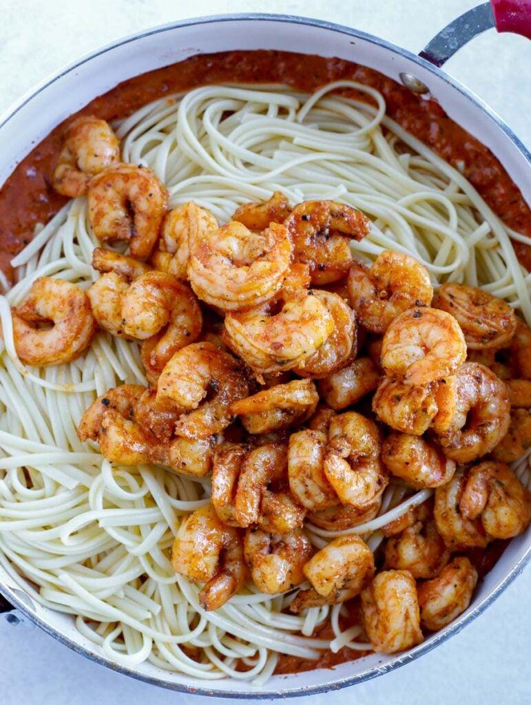 Shrimp on top of noodles in a skillet.