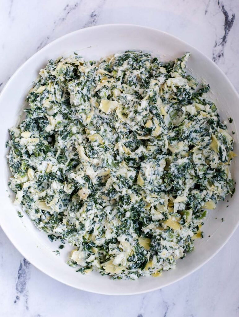 spinach artichoke stuffing ingredients in a plate after mixing