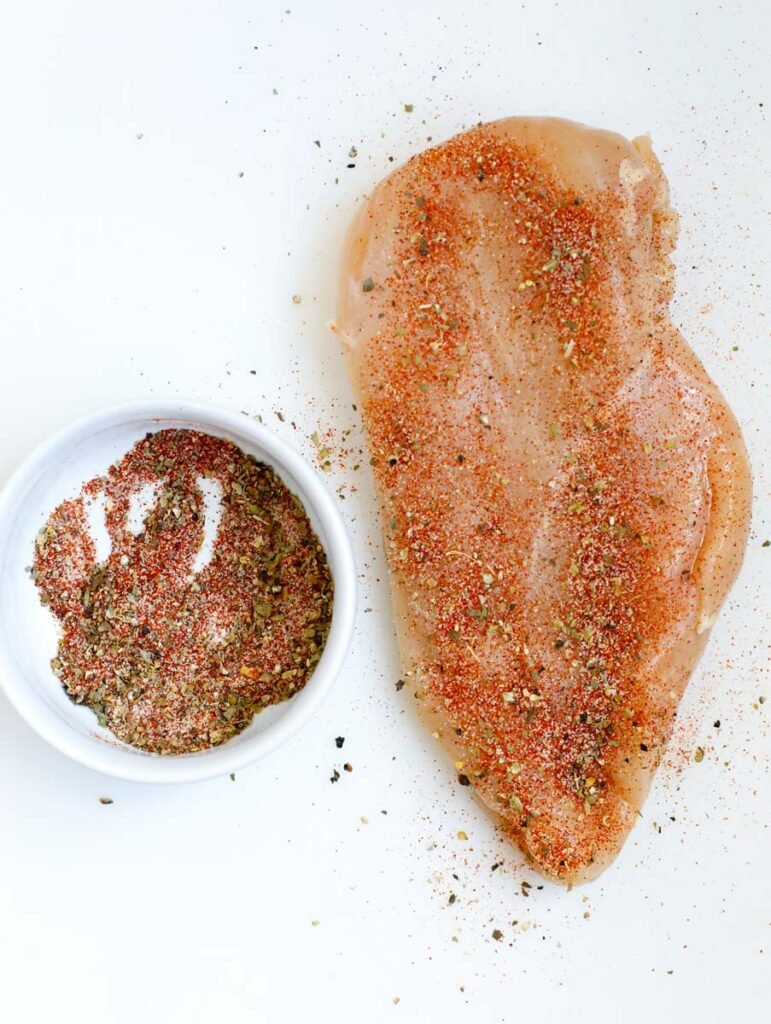 Top down shot of raw chicken breast with seasoning on it.