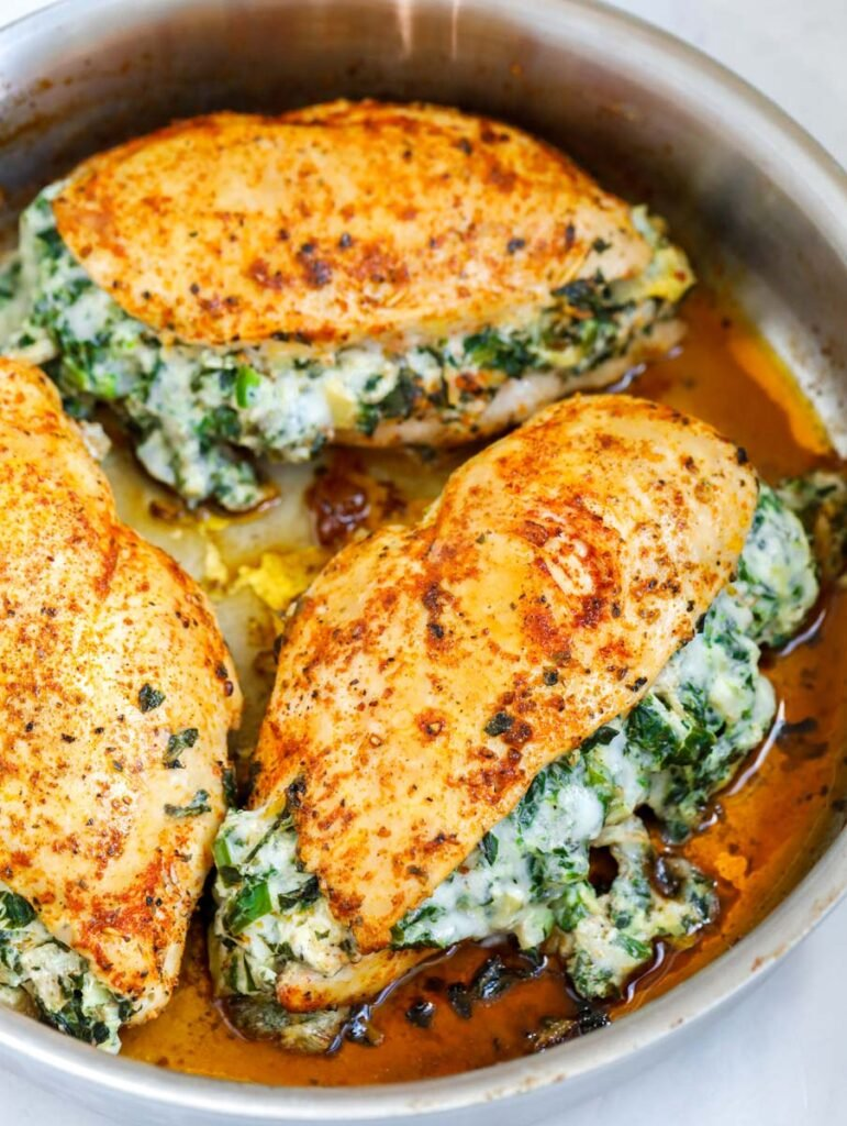 Side shot of three spinach stuffed chicken breasts in a pan.