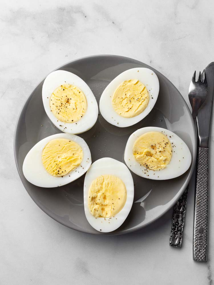 hard boiled eggs sliced through showing the yolk and seasoned with pepper