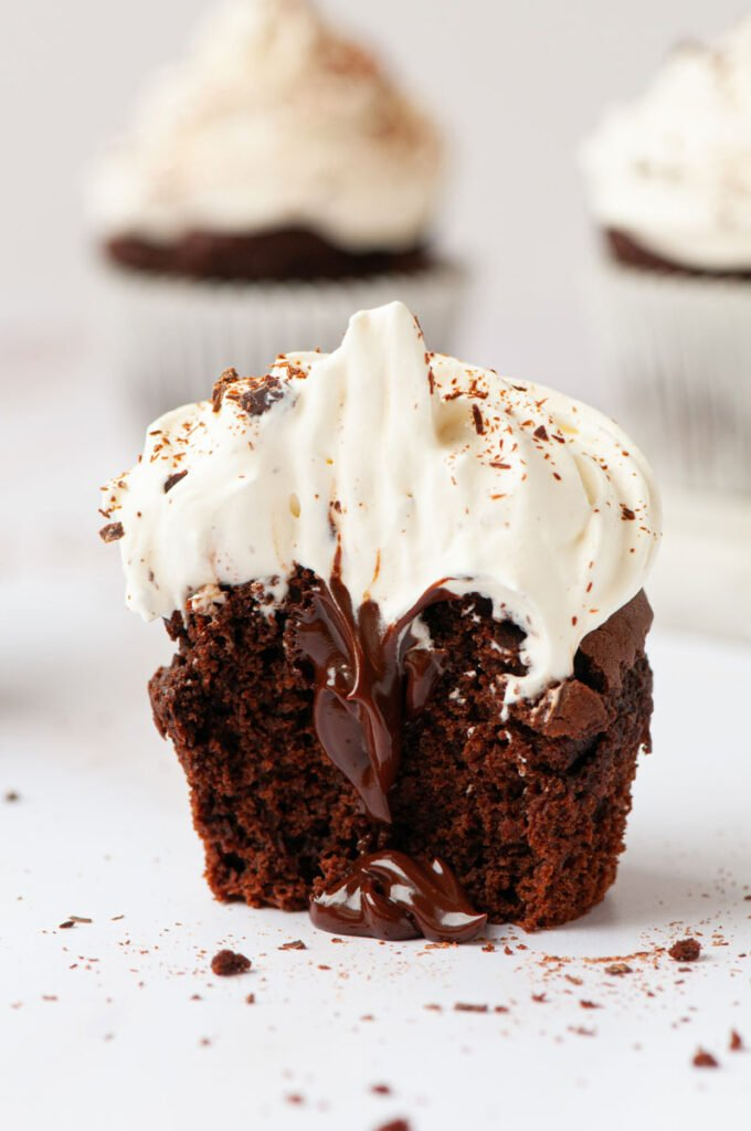 chocolate cupcake with whip cream on top and chocolate in the middle and a bite taken out of it