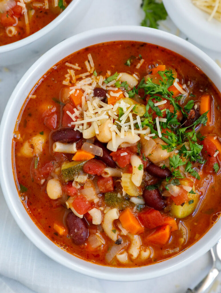 Top down view of a bowl of vegetable minestrone soup.