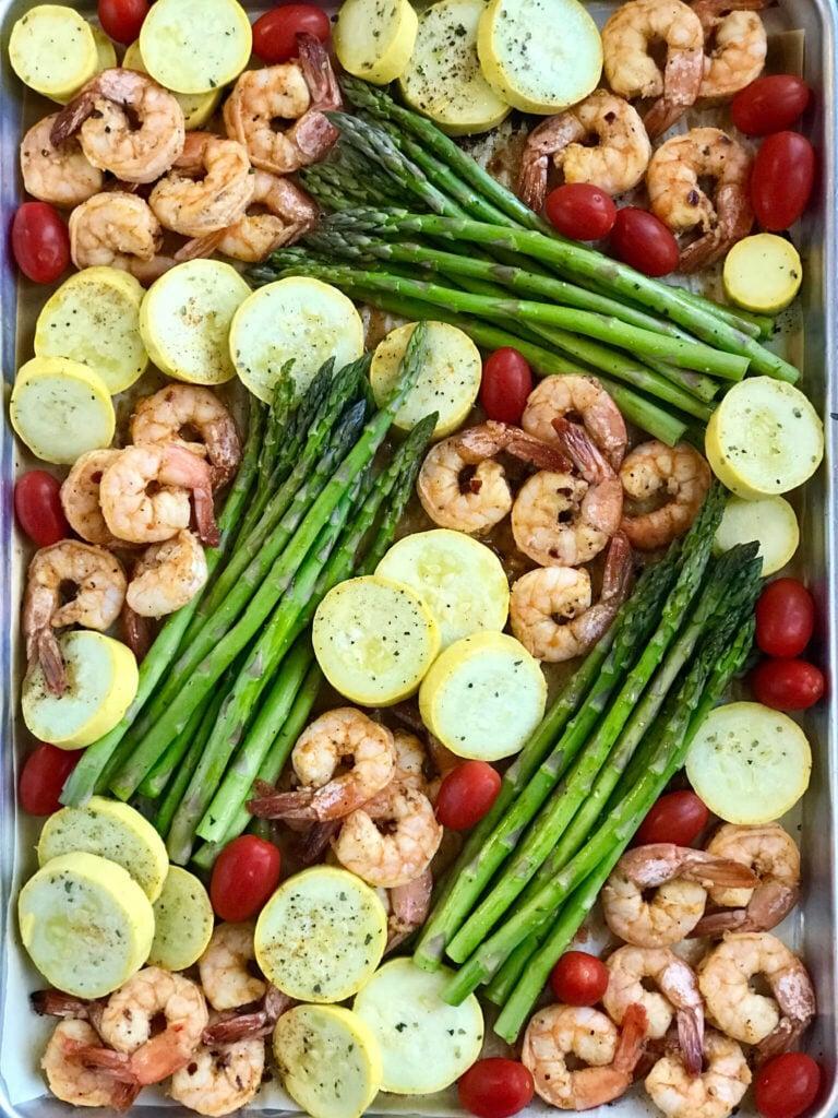 A sheet pan of sriracha garlic shrimp, squash, tomatoes, and asparagus