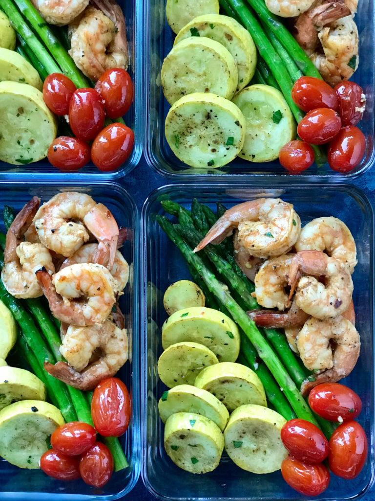 Sriracha Garlic Shrimp in small meal prep containers with squash, tomatoes, and asparagus
