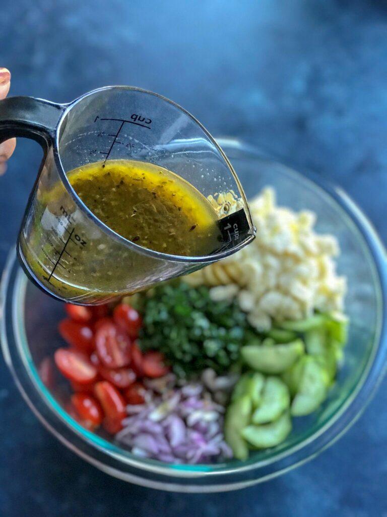 Pouring lemon vinaigrette on the pasta salad ingredients