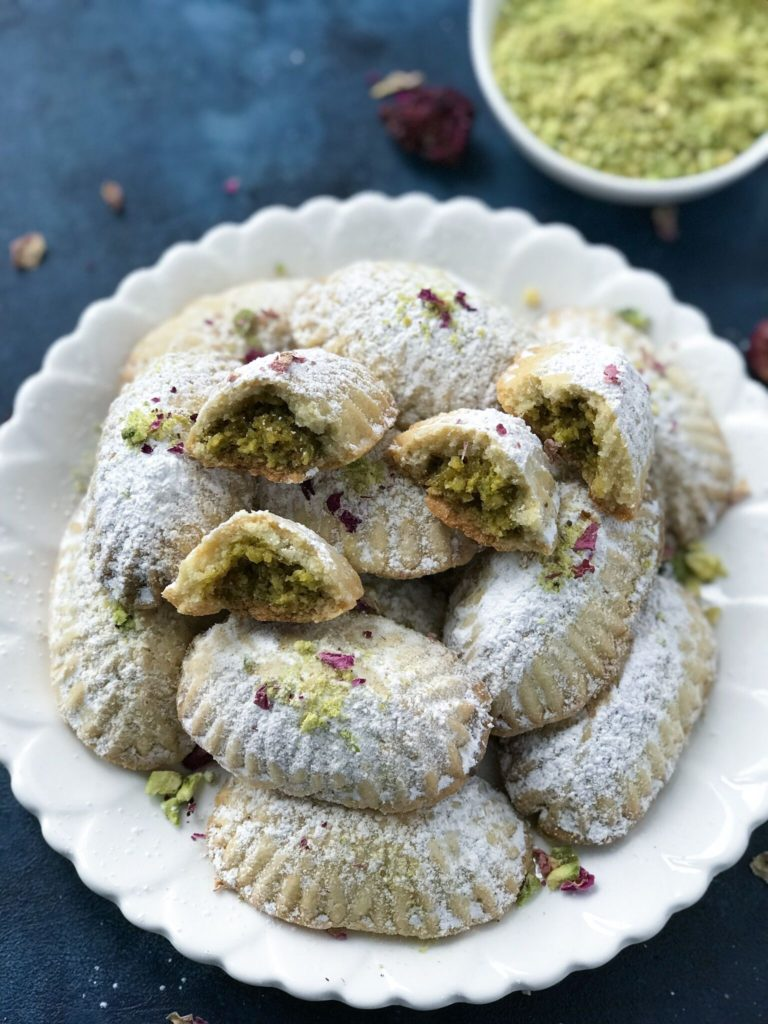 Pistachio Maamoul Cookies ( معمول بالفستق ) on a white plate with some broken in half
