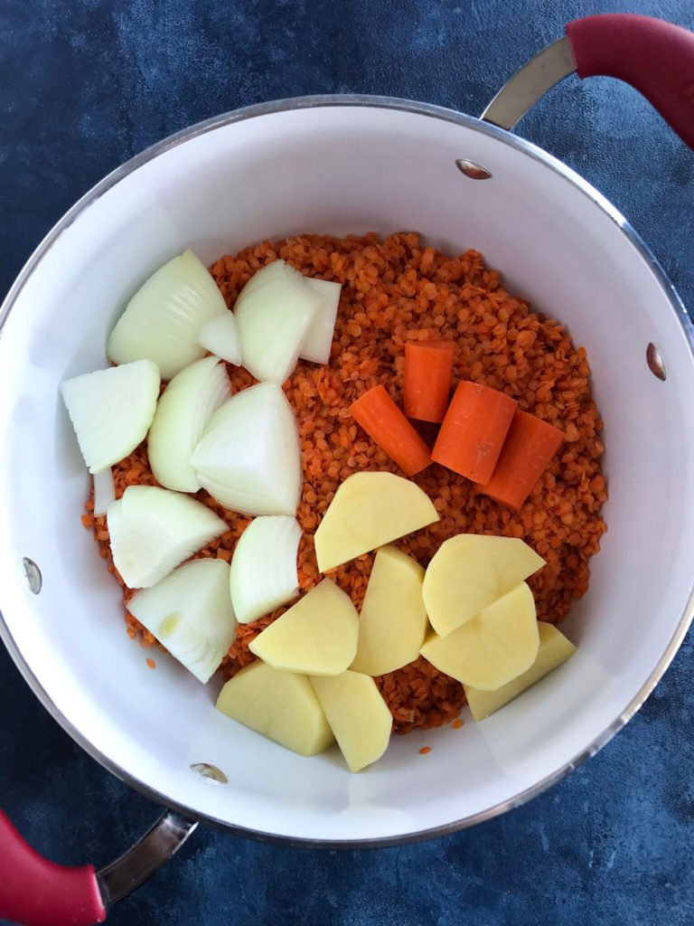The vegetables and red lentils in a pot.