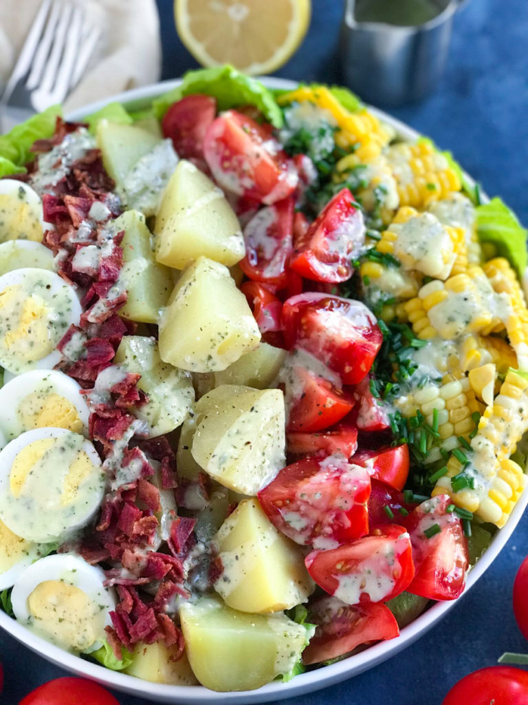 The salad with dressing drizzled on it