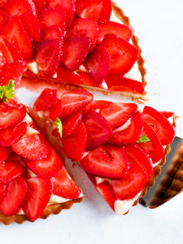 Strawberry French Tarte with a slice being taken out.