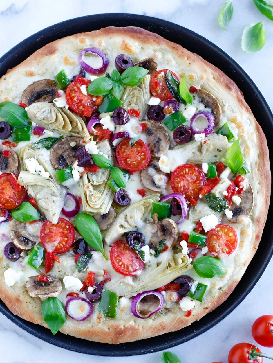 Mediterranean Veggie Pizza with delicious pesto sauce, topped with some alfredo sauce, and packed with fresh veggies and cheese.
