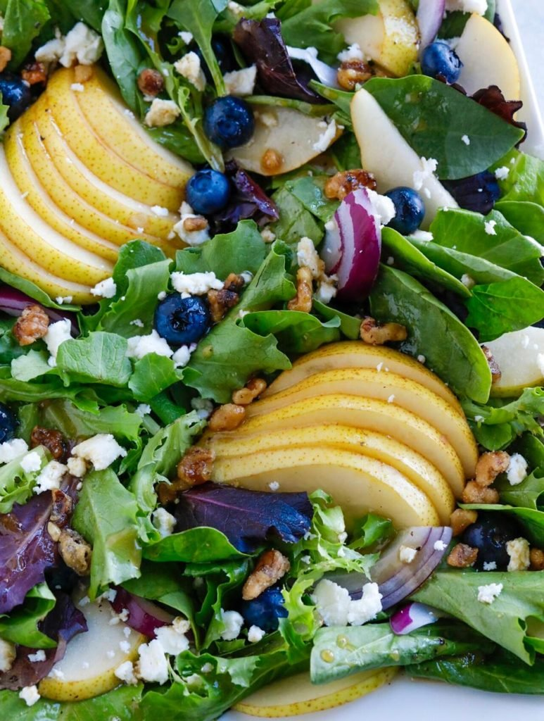 pear and blueberry salad on a white plate.