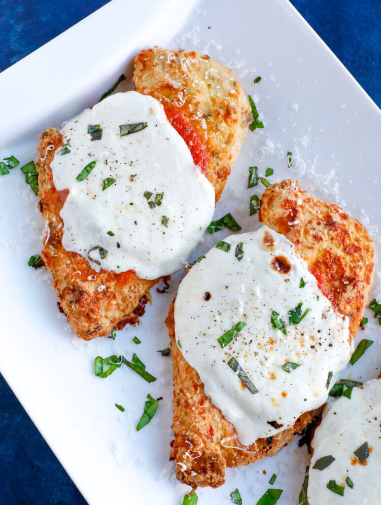 Overhead shot of Baked chicken parm with cheese and basil topping