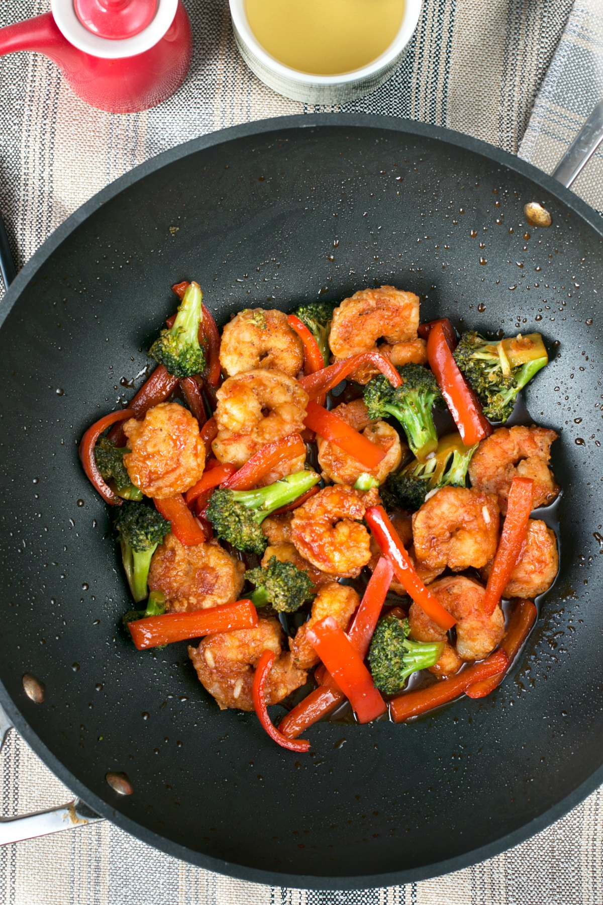 Honey sriracha shrimp peppers and broccoli being sauteed in a wok