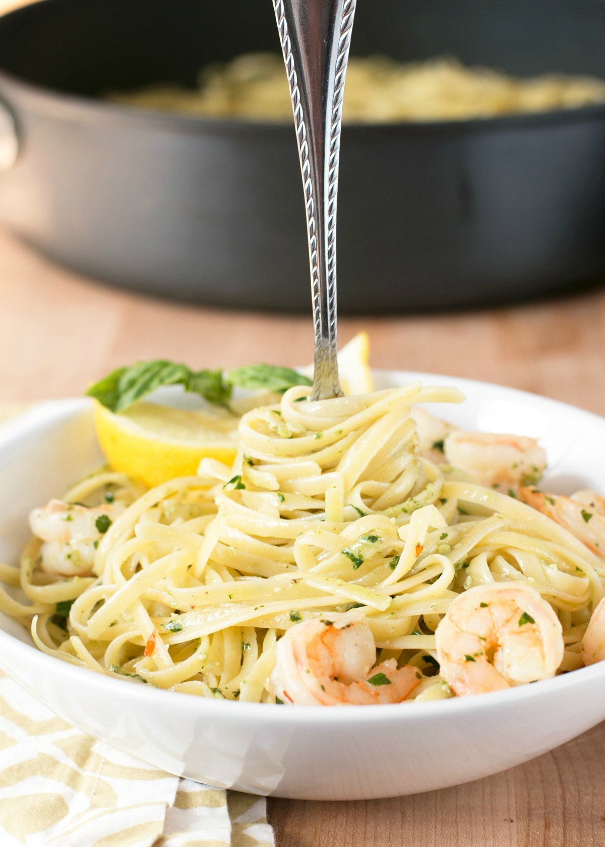 Large white bowl of pesto shrimp scampi pasta with a fork in the center