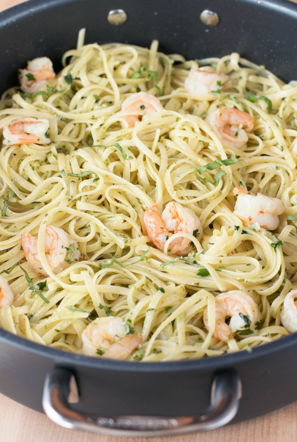 Pesto shrimp scampi with pasta being tossed together in a large stockpot